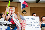 "May 29 - TEMPE, AZ: A man from Texas shows support for Arizona's SB1070 in Tempe, AZ, Saturday. About 3,000 people attended a ""Buy Cott Arizona"" rally at Tempe Diablo Stadium in Tempe, AZ Saturday night. The rally was organized by members of the Arizona Tea Party movement to show support for Arizona law SB1070. SB1070 makes it an Arizona state crime to be in the US illegally and requires that immigrants carry papers with them at all times and present to law enforcement when asked to. Critics of the law say it will lead to racial profiling, harassment of Hispanics and usurps the federal role in immigration enforcement. Supporters of the law say it merely brings Arizona law into line with existing federal laws.  Photo by Jack Kurtz"