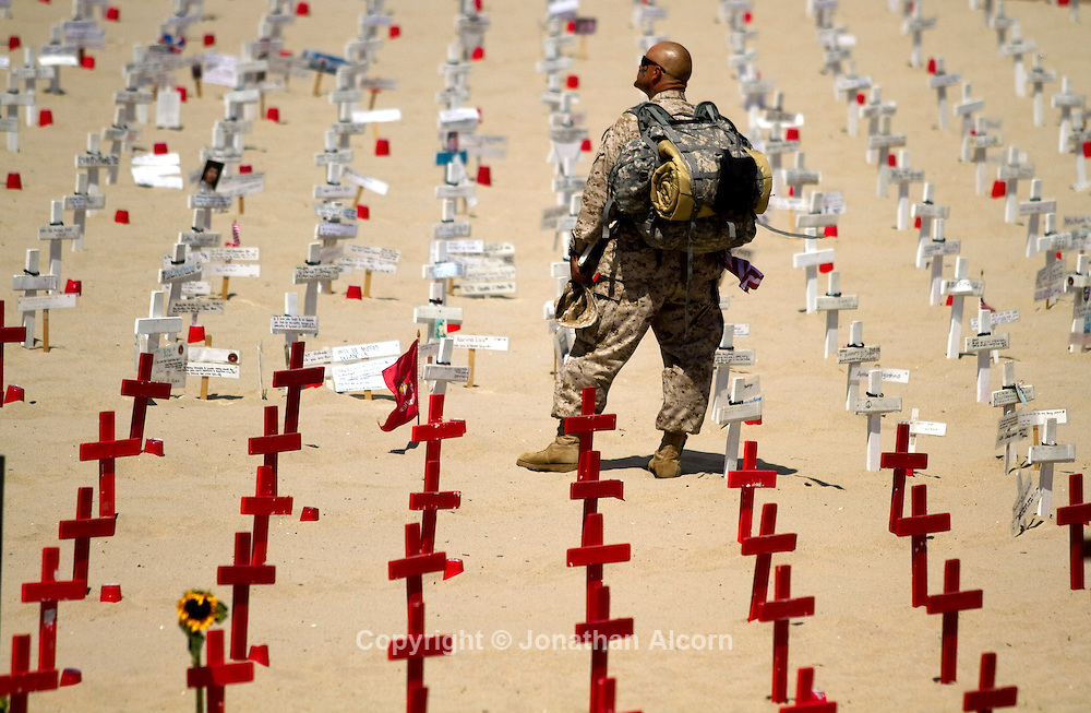 "A veteran dressed in fatigues pauses at the ""Arlington West"" Memorial on Sunday, May 29, 2011.  Small wooden crosses, one for each U.S. military member who has died in either Iraq or Afghanistan, are placed in the sand on Santa Monica Beach Sunday from sunrise to sunset, a temporary memorial appears next to the world-famous pier at Santa Monica, California. This memorial, known as Arlington West is a project of Veterans For Peace"