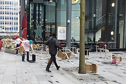 © Licensed to London News Pictures . 22/03/2013 . Manchester , UK . Staff scramble to collect furniture that's blown over in heavy wind . Heavy gusts of wind blow chairs and tables over outside a branch of Pret a Manger in Spinningfields in Manchester this (22nd March) afternoon . Heavy wind , rain and snow across the north of the UK is causing disruption today (22nd March) . Photo credit : Joel Goodman/LNP