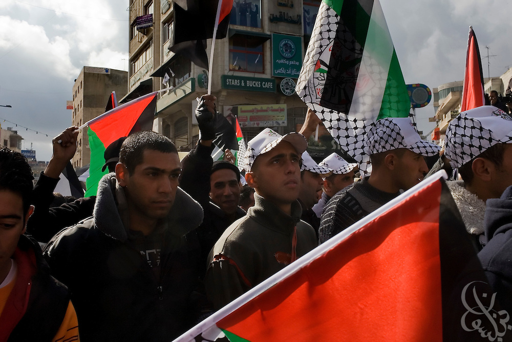 Palestinians carry flags and chant slogans during a protest against the Israeli incursion into Gaza January 09, 2009 in the West Bank City of Ramallah. Scuffles broke out during the protest of more than 10,000 marchers between supporters of Fatah, and Hamas.