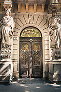 Brown wooden door with stone surround, large statues in front, Budapest Hungary