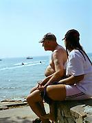 A couple holding hands on Pattaya Beach Promenade.