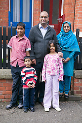 Young family standing outside the front door to their home,
