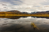 Alaska Range and Gulkana Glacier reflected in pond near Paxson in Interior Alaska. Autumn. Morning.