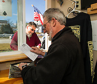 Bob Davis completes Paul Peterson's registration for the 2016 Great Meredith Rotary Ice Fishing Derby on Friday morning at Derby Headquarters in Meredith Bay.  (Karen Bobotas/for the Laconia Daily Sun)