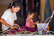 "03 DECEMBER 2012 - BANGKOK, THAILAND:   A woman strips electrical wire out of a closed bar in the ""Washington Square' district in Bangkok while her child sits nearby. Workers live in the buildings they are demolishing until the buildings are completely uninhabitable. Washington Square was a notorious adult ""entertainment"" and red light district on Sukhumvit Soi 22 in Bangkok. Many of the bars and massage parlors catered in the district to older American and European men and opened in the 1960's when Bangkok was a ""R&R"" destination for American servicemen in Vietnam. It's being torn down to make way for new high rise hotels and condominiums.     PHOTO BY JACK KURTZ"