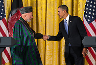 U.S. President Barack Obama, right, and Afghanistan President Hamid Karzai, left, reach out to shake hands following a joint press conference in the East Room of the White House January 11, 2013 in Washington D.C.  Obama earlier held an expanded bilateral meeting with Karzai in the Oval Office.   Photo Ken Cedeno.