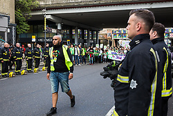 London, UK. 14th June, 2018. Zeyad Cred walks through a guard of honour prepared by the London Fire Brigade for the Grenfell Silent March through West Kensington on the first anniversary of the Grenfell Tower fire. 72 people died in the Grenfell Tower fire and over 70 were injured.