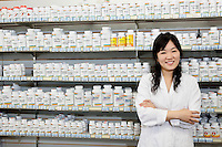 Portrait of a happy young woman with arms crossed in front of pills shelf in drugstore