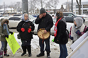 Kelly Kiyoshk finishes a heartfelt prayer and is about to bigin drumming for a roundhouse dance at a prayer vigil in Windsor, Ontario, Canada in response to the not guilty verdict in the Colten Boushie case. Loreena Shepley-Garvey, Kiniwdewiwinkwe Beth Cook, and two children react to an emotional moment.