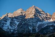 The Maroon Bells are two adjacent peaks of the Elk Mountains: Maroon Peak 14,163 feet on left, seen behind North Maroon Peak 14,019 feet, in Maroon Bells-Snowmass Wilderness of White River National Forest. The mountains are on the border between Pitkin County and Gunnison County, about 12 miles southwest of Aspen, in Colorado, USA.