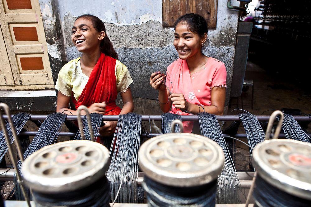 2 young women make plastic string in the city of Bhavnagar, Gujarati State. The Shaishav Trust is trying to provide education and support for children in child labour.