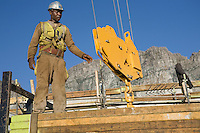 Workman lowers hook block to lift stack of planks