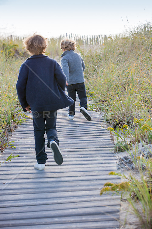 two boys running down a wooden beach boardwalk