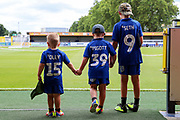 Young AFC Wimbledon fans walking onto the pitch wearing AFC Wimbledon shirts during the EFL Sky Bet League 1 match between AFC Wimbledon and Rotherham United at the Cherry Red Records Stadium, Kingston, England on 3 August 2019.