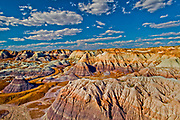 """The Painted Desert is a spectacular badlands running from near the east end of Grand Canyon National Park southeast into the Petrified Forest National Park. The desert is about 120 miles (190 km) long by about 60 miles (97 km) wide, making it roughly 7,500 square miles (19,425 km2) in area.  The view shown here is from the north portion of The Petrified Forest National Park. The Painted Desert is known for its brilliant and varied colors, including the unusual shades of lavender evident in this photograph.  <br /> <br /> The area resides within a strong rain shadow, giving it a cold desert climate with hot, dry summers and cold, virtually snow-free winters. The annual precipitation is the lowest in northern Arizona and in many places is lower even than Phoenix.<br /> <br /> The desert is composed of stratified layers of easily erodible siltstone, mudstone, and shale of the Triassic Chinle Formation. These fine-grained rock layers contain abundant iron and manganese compounds which provide the pigments for the various colors of the region. The erosion of these layers has resulted in the formation of the characteristic badlands topography of the region. Numerous layers of silicic volcanic ash occur in the Chinle and provide the silica for the petrified logs of the area. An assortment of fossilized prehistoric plants and animals are also found in the region, as well as dinosaur tracks and evidence of early human habitation.<br /> <br /> Desert was named by an expedition under Francisco Vázquez de Coronado on his 1540 quest to find the Seven Cities of Cibola, which he located some forty miles east of The Petrified Forest National Park. Finding that the cities were not made of gold as expected, Coronado sent an expedition to find the Colorado River to resupply his group. Passing through the wonderland of colors, they named the area """"El Desierto Pintado"""", The Painted Desert."""