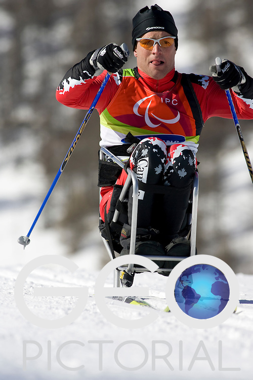 PRAGELATO PLAN, ITALY - MARCH 12: Jimmy Pelletier of Canada competes in the Mens Cross Country Skiing 5km Sitting on Day 2 of the 2006 Turin Winter Paralympic Games on March 12, 2006 in Pragelato Plan, Italy.