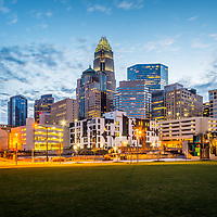 Downtown Charlotte skyline at dusk photo with Romare Bearden Park and Charlotte city buildings against a blue sky. Charlotte is a major city in North Carolina in the Eastern United States.