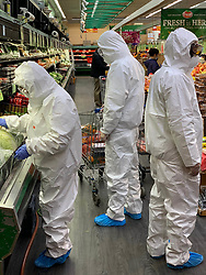 People wear hazmat suits while food shopping in Flushing, Queens during the Coronavirus Pandemic
