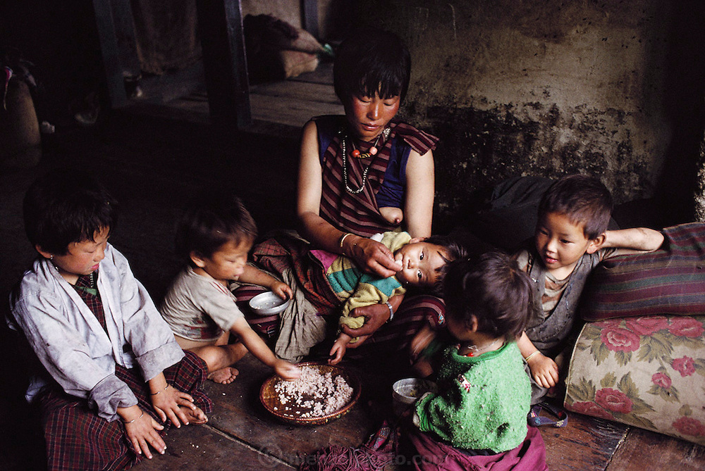 Sangay, her children, and young sister Zekom (second from right) eat a snack of toasted grain. Shingkhey, Bhutan. From Peter Menzel's Material World Project.