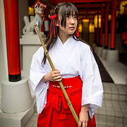 "TOKYO, JAPAN - JUNE 27 : A shrine maiden posed for a portrait in front of the entrance of Akihabara shrine in Akihabara, Tokyo, Japan. June 27, 2016. A newly opened Akihabara Shrine offers a memorial services for ""deceased"" anime figures. Photo by Richard Atrero de Guzman"