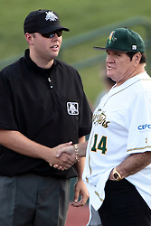 09 July 2015: Pete Rose know affectionately to fans as Charlie Hustle the current Major League Baseball all time hits leader exits the CornBelters dugout as manager for the night to take his place in the first base coaches box shakes hands and makes some small talk with 1st base umpire Brad Swanson. Pete Rose night during a Frontier League Baseball game between the Schaumburg Boomers and the Normal CornBelters at Corn Crib Stadium on the campus of Heartland Community College in Normal Illinois