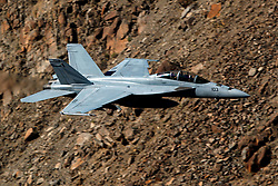 United States Navy Boeing F/A-18F Super Hornet (NH-103) from VFA-14 Tophatters squadron Naval Air Station Lemoore flies low level through the Jedi Transition, Star Wars Canyon, Death Valley National Park, California, United States of America