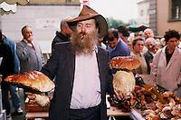 October 1992, Alba, Italy --- Grocer Holding Large Porcini Mushrooms --- Image by © Owen Franken - Photograph by Owen Franken