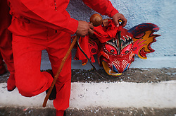 A man takes of his devil mask and rests during the Corpus Christi celebration.  Venezuela is dotted with towns that celebrate Corpus Christi with a two day devil dancing celebration.  Community members, dressed as devils, first dance in front of the Church asking for forgiveness from their sins.  They then parade through the town dancing making stops at a various homes along the way.  The houses all have stands with religious symbols and candles inf front of which  the Devil Dancers pray and beg forgiveness    It is considered an honor to dance during the celebration.