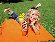young fresh teenager lying on blanket with feet up in park