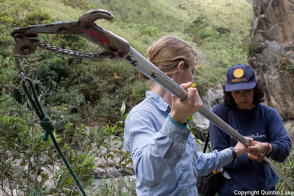 Theresa Meacham and Norma Salinas assemble the telescopic pruner for collecting an orchid sample adjacent to the Interoceanic Highway