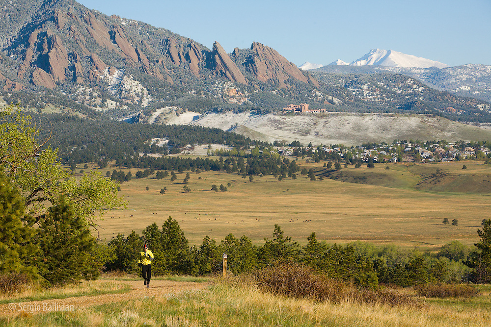 A mid-adult man trail running  on Marshall Mesa outside Boulder, Colorado