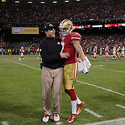 San Francisco 49ers head coach Jim Harbaugh congratulates quarterback Colin Kaepernick after his 56-yard touchdown run in the third quarter against the Green Bay Packers in the NFC Divisional Playoff game at Candlestick Park in San Francisco, California.