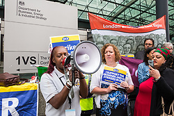 London, UK. 15 July, 2019. Barista Ana Joaquim addresses catering and cleaning staff belonging to the PCS trade union and outsourced to work at the Department for Business, Energy and Industrial Strategy (BEIS) via contractors ISS World and Aramark on the picket line outside the Government department after walking out on an indefinite strike for the London Living Wage, terms and conditions comparable to the civil servants they work alongside and an end to outsourcing.