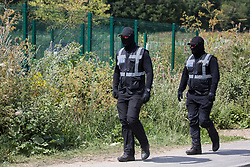 Harefield, UK. 22 July, 2020. Masked HS2 security guards walk along Harvil Road to a site for the HS2 high-speed rail link which had been occupied by activists from HS2 Rebellion in order to hinder tree felling works. Environmental activists continue to protest against HS2, which is currently projected to cost £106bn and will remain a net contributor to CO2 emissions during its projected 120-year lifespan, from a series of wildlife protection camps along its route.