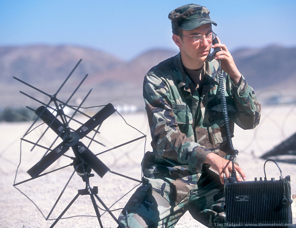 SPC Timothy Severson tests a TACSAC, a radio that uses satellites to communicate, at the National Training Center in Ft. Irwin, Calif. on Friday, July 26, 2002. While Severson was speaking with a communications center only a few hundred yards away, he were testing the equipment in preparation for going to 'war' at Ft. Irwin for the Millennium Challenge 2002 Experiment (MCO2)...Part of the military transformation, MC02 is testing all branches of the military in the largest ever live and virtual battle being played out across the nation through August 15, 2002. The goal is to see how well the different branches operate together under a joint command that shares intelligence and resources in an effort to put the right forces in the right place at the right time so as to minimze the amount of fighting that is necessary to protect U.S. interests abroad.
