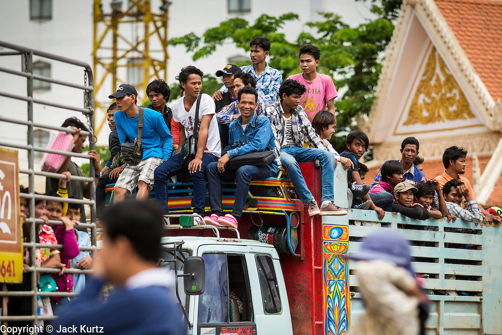 16 JUNE 2014 - POIPET, CAMBODIA: Cambodian migrants arrive in Poipet, Cambodia on top of a truck after returning to Cambodia from Thailand. More than 150,000 Cambodian migrant workers and their families have left Thailand since June 12. The exodus started when rumors circulated in the Cambodian migrant community that the Thai junta was going to crack down on undocumented workers. About 40,000 Cambodians were expected to return to Cambodia today. The mass exodus has stressed resources on both sides of the Thai/Cambodian border. The Cambodian town of Poipet has been over run with returning migrants. On the Thai side, in Aranyaprathet, the bus and train station has been flooded with Cambodians taking all of their possessions back to Cambodia.  PHOTO BY JACK KURTZ