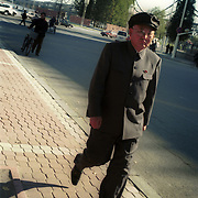 Dandong city, China, 11-2003..A North Korean man strolls in China's Dandong city, just across the border from North Korea...China help North Korea fight the Korean War in the 1950s and continue to have a defence treaty with the Stalinist country...Ruled by the messianic leader Kim Il Sung and his son Kim Jong Il since 1948, North Korea has stubbornly stuck to its juche (self-reliance) ideology and siege mentality, imposing one Stalinist economic plan after another. Floods, droughts and mismanagement in the 1990s plunged the country into a preventable famine, killing up to three million, or 13 percent of the population. It now depends heavily on Chinese aid...