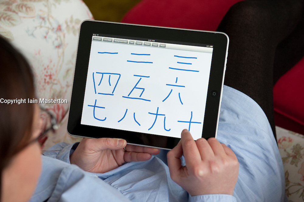 Woman writing Chinese characters for number from 1 to 10 on an iPad tablet computer