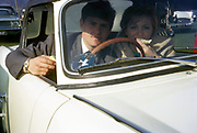 Young courting couple eating in their white sports car UK 1969