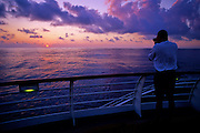 Tourist on ship photographing sunrise near Maui.
