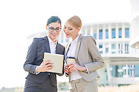 Happy businesswomen using tablet PC outside office building