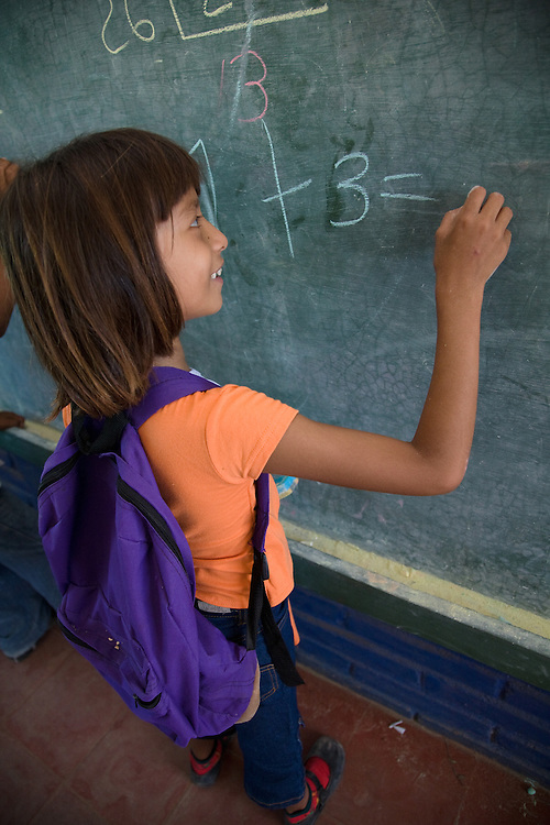 Central America, Nicaragua, Granada.  Girl writing on blackboard in school classroom in  Santa Ana de Malacos.  MR