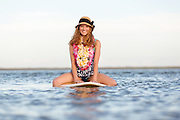 Beautiful curly red head young woman on surfboard at beach