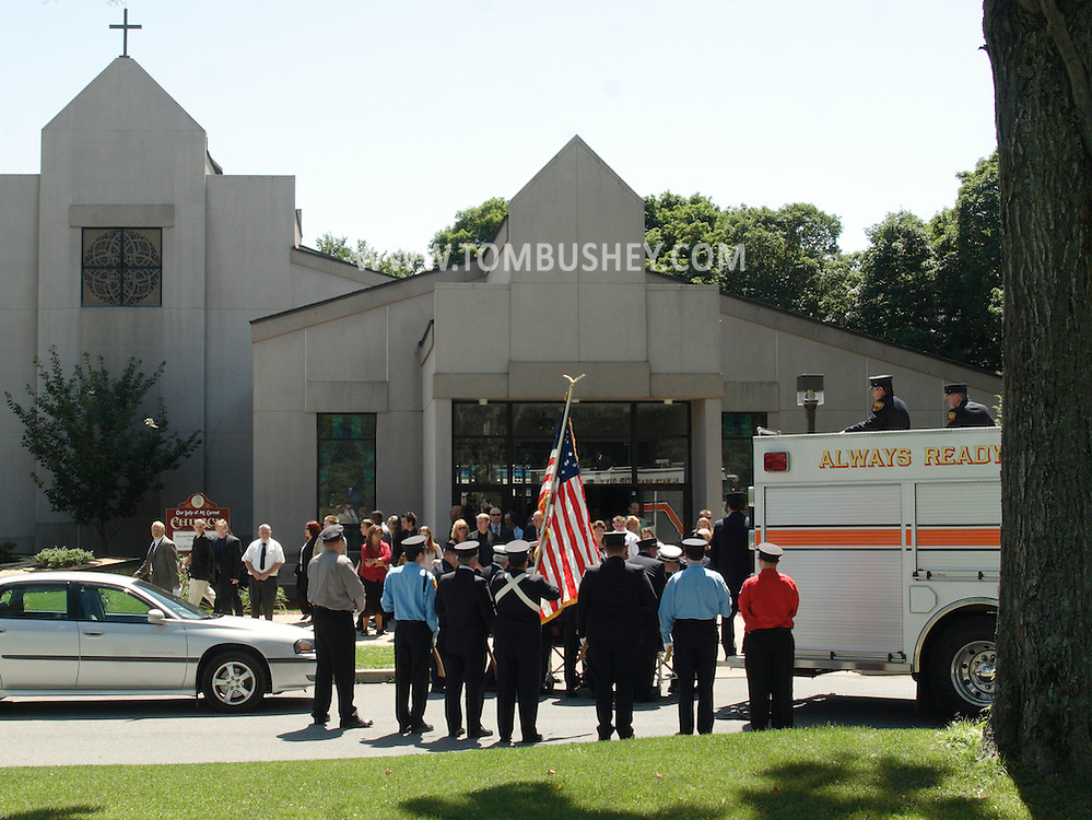 Middletown, NY - Mourners leave Our Lady of Mount Carmel Church after funeral services for Donald H. Kimble Jr., a former chief of the Middletown Fire Department, on Aug. 11, 2007. Firefighters in uniform are getting ready to place the casket on the fire truck at right..