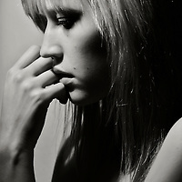 Black and white portrait of young woman looking down in a pensive pose
