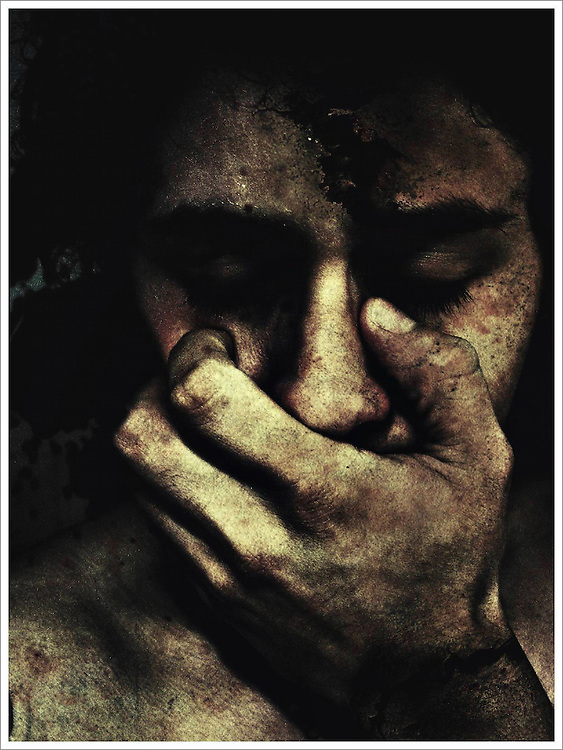 Close up of a young mans face with a hand covering his mouth