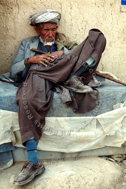 An Afghan elder is sleeping on the streets of Bamiyan's new bazaar. The cliff where once stood the Western Buddha (55m - 'Male') is photographed after sunset in Bamiyan, Afghanistan, an area mostly populated by Hazaras. The Buddhas of Bamiyan were two 6th century monumental statues of standing Buddhas carved into the side of a cliff in the Bamiyan valley in the Hazarajat region of central Afghanistan, situated 230 km northwest of Kabul at an altitude of 2500 meters. The statues represented the classic blended style of Gandhara art. The main bodies were hewn directly from the sandstone cliffs, but details were modelled in mud mixed with straw, coated with stucco. Amid widespread international condemnation, the smaller statues (55 and 39 meters respectively) were intentionally dynamited and destroyed in 2001 by the Taliban because they believed them to be un-Islamic idols. Once a stopping point along the Silk Road between China and the Middle East, researchers think Bamiyan was the site of monasteries housing as many as 5,000 monks during its peak as a Buddhist centre in the 6th and 7th centuries. It is now a UNESCO Heritage Site since 2003. Archaeologists from various countries across the world have been engaged in preservation, general maintenance around the site and renovation. Professor Tarzi, a notable An Afghan-born archaeologist from France, and a teacher in Strasbourg University, has been searching for a legendary 300m Sleeping Buddha statue in various sites between the original standing ones, as documented in the old account of a renowned Chinese scholar, Xuanzang, visiting the area in the 7th century. Professor Tarzi worked on projects to restore the other Bamiyan Buddhas in the late 1970s and has spent most of his career researching the existence of the missing giant Buddha in the valley.