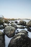 White foam from the sea encircles the golden stones at the beach   Hvitt skum fra havet omfavner de gyldne stenene på stranden