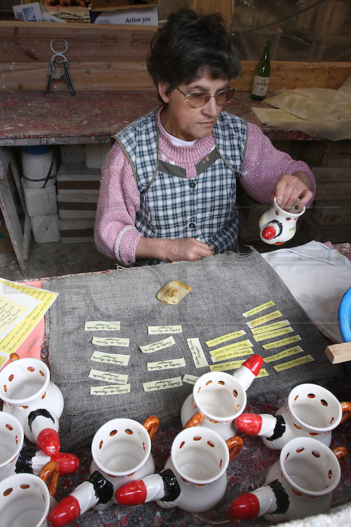 The wife of Francisco Silva with erotic ceramic mugs containing phallus created by himself in his atelier at Chao da Parada, in Caldas da Rainha city. He is one of the last artisans of this kind of erotic pottery traditional to Caldas da Rainha, in the center region of Portugal.